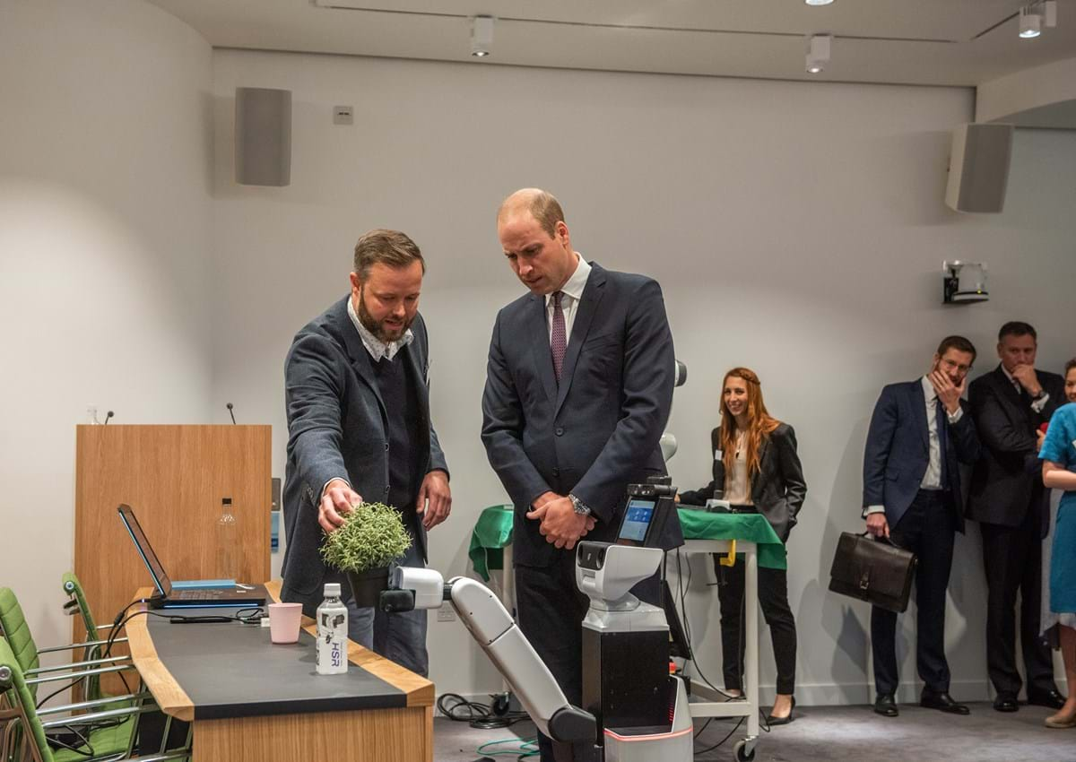 Duke Of Cambridge and Lars Kunze looking at the HSR Robot at Keble College.
